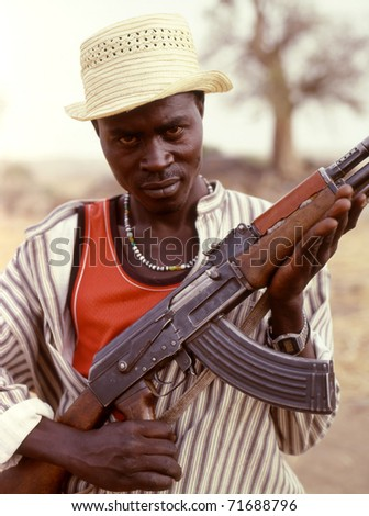 NUBA MOUNTAINS, SUDAN - JANUARY 13: A member of the Sudanese Nuba holds a Kalashnikov on January 13, 2008 in the Nuba mountains, Sudan. By 1991 the Nuba fought alone without supplies, depending solely on local support.