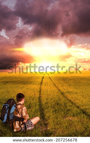 """Nuclear explosion and the young man did not reach his goal, sitting and looking hopelessly at the """"end of life"""". beginning of the End - stock photo"""