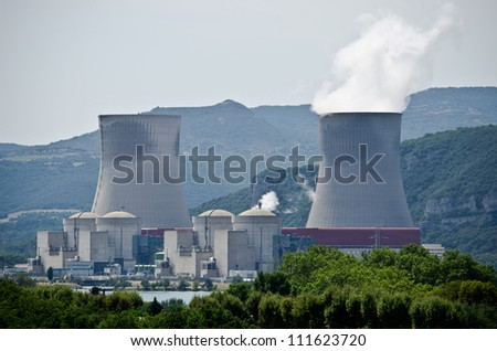 Nuclear plant generating electricity. Two towers among hills - stock photo