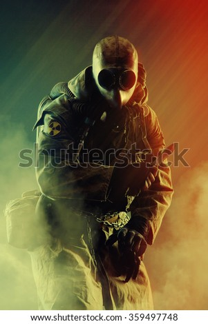 Nuclear post apocalypse. Studio shot of survivor in tatters and gas mask - stock photo