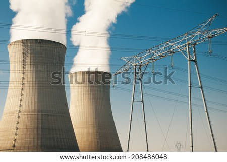 nuclear power plant cooling towers and high voltage pylon - stock photo