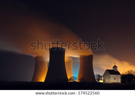 Nuclear power plant cooling towers with steam behind a small chapel