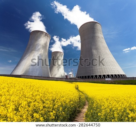 Nuclear power plant Dukovany with golden flowering field of rapeseed - Czech Republic - two possibility for production of energy - stock photo