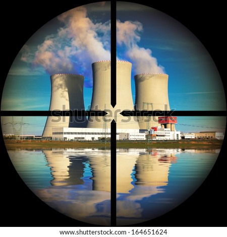 Nuclear power plant in a terrorist's weapon gunsight. Nuclear safety concept.  - stock photo