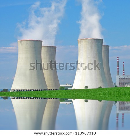 Nuclear power plant reflecting on the lake in perfect summer weather. - stock photo