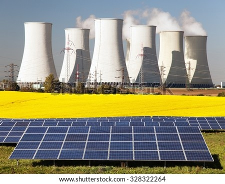 Nuclear power plant with golden glowering field of rapeseed and photovoltaic sunny power plant - Three possibility for production of electric energy