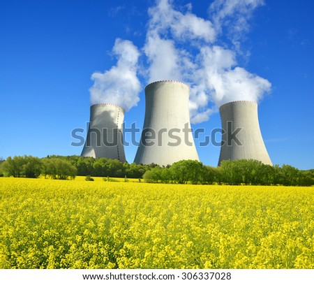 Nuclear power plant with rapeseed field - stock photo