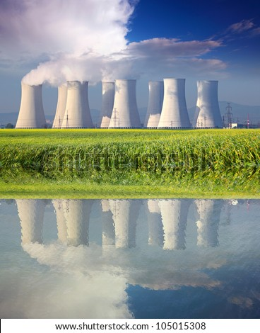 Nuclear power plant with reflection in water at spring - stock photo