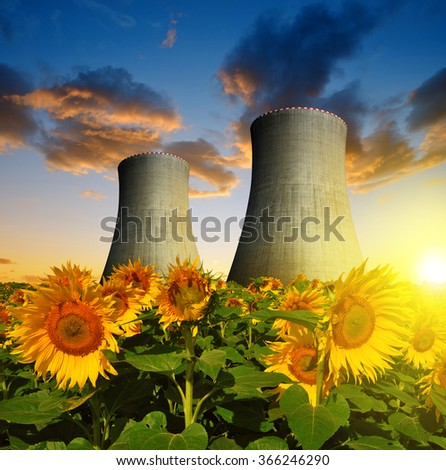 Nuclear power plant with sunflower field in the sunset - stock photo