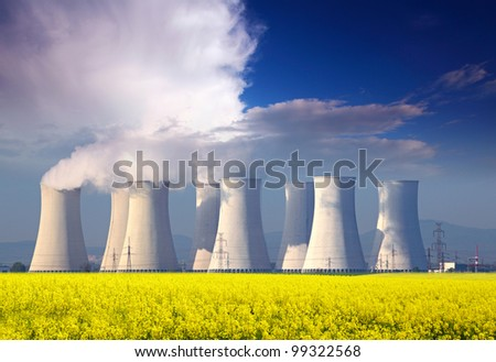 Nuclear power plant with yellow field and big blue clouds. - stock photo