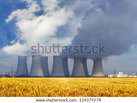 Nuclear power plant with yellow field and sun - stock photo