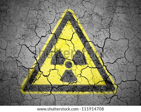 Nuclear radiation sign drawn on cracked ground with vignette - stock photo