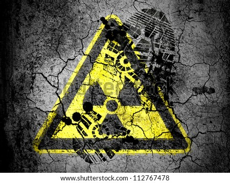Nuclear radiation sign drawn on cracked ground with vignette with dirty oil footprint over it - stock photo