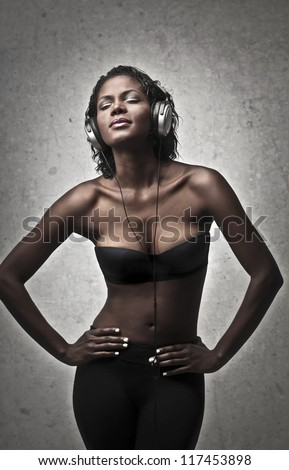 Nude black girl with a pair of headphones - stock photo