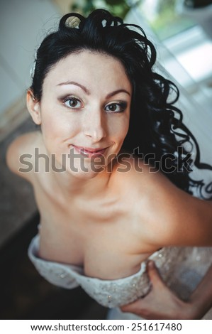Nude bride Striptease. Beautiful girl in white lingerie play with her wedding dress. Young cheerful bride posing in white lingerie. - stock photo