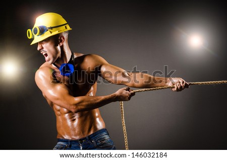 Nude builder pulling rope in darkness - stock photo