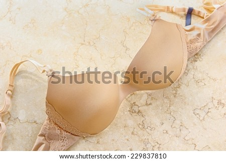 Nude color lace bra on marble. - stock photo