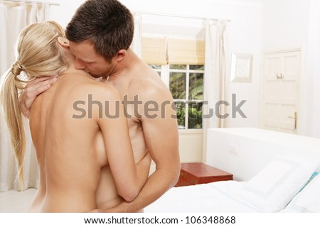 Nude couple hugging in bedroom.