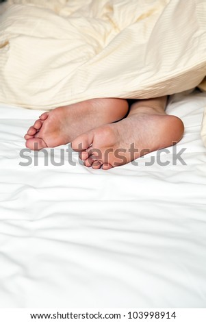 nude feets looking out of blanket in bed