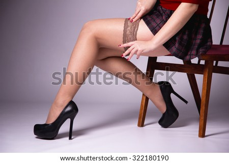 Nude female legs, slender legs, puts a nylon stocking, she wears stockings sitting on a chair, smooth skin, healthy skin, red manicure, high heels, European style, pair of legs, attractive shape.