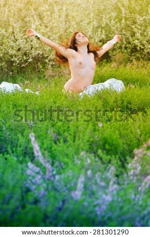 Nude girl running in a lush garden - stock photo