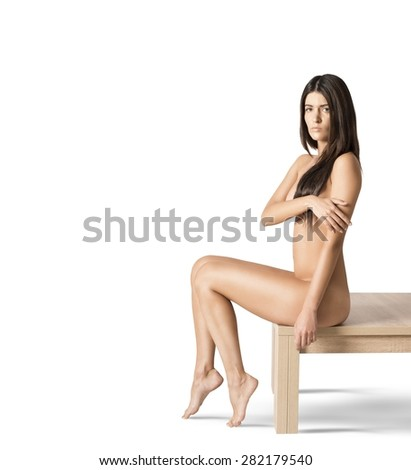 Nude model sitting on a wooden table - stock photo