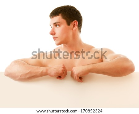Nude muscular man covering with a copy space blank board isolated on white - stock photo