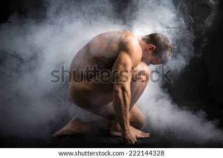Nude Profile of Young Muscle Man Crouching in Fog in Studio with Black Background - stock photo
