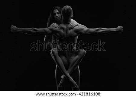 Nude sexy couple. Art photo of young adult man and woman. High contrast black and white muscular naked body on black background - stock photo