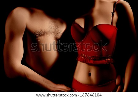 Nude sexy couple in darkness. Erotic Woman in red lingerie and topless man torso close up - stock photo
