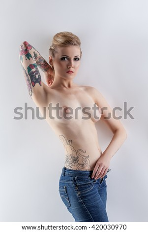 Nude. Topless girl with tattoos posing at camera - stock photo