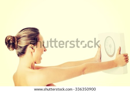 Nude topless woman holding scale - stock photo