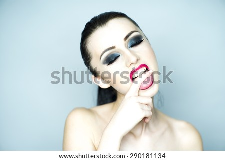 Nude vamp brunette girl with bright makeup biting finger standing on light grey background copyspace, horizontal picture - stock photo