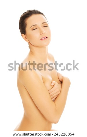 Nude woman covering her breast with cross hands