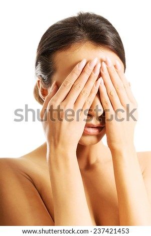 Nude woman covering her eyes because of shame.