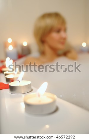 nude woman in foamy bath with petals of roses and by light of candles - stock photo