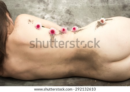Nude woman lying sideways her back facing camera with arms covering breasts and flowers placed along body