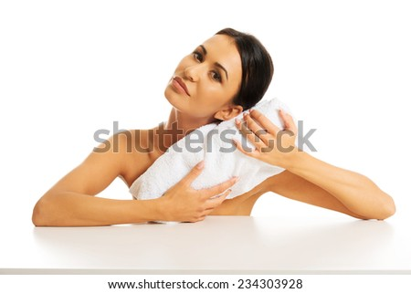 Nude woman rests her head on a rolled towel. - stock photo
