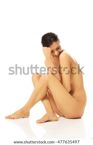 Nude woman sitting and looking down