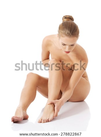 Nude woman sitting on the floor, touching her foot bone.