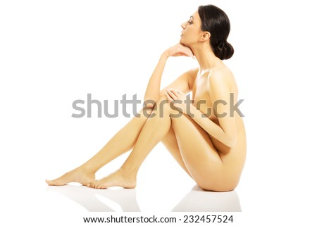 Nude woman sitting with her knees close to the chest and holding hand under chin. - stock photo