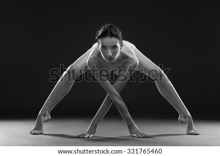 Nude yoga. Beautiful sexy body of young woman on gray background. Black and white photography - stock photo