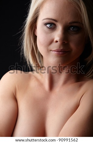 Nude young adult caucasian woman with blonde hair and blue eyes on a dark background - stock photo
