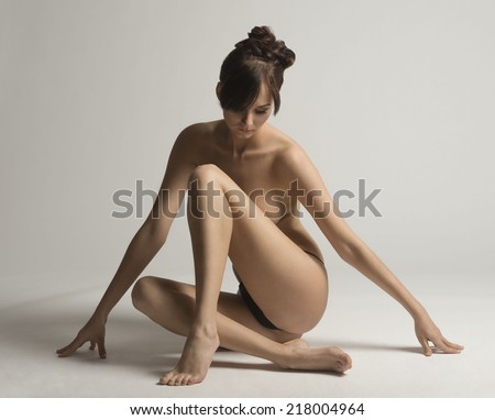 Nude, young, natural, sensual woman with brown hair and hair bun posing in studio   - stock photo