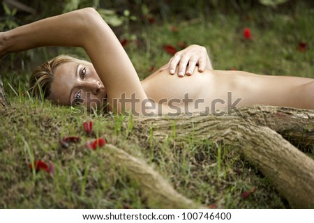 Nude young woman laying down on green grass and red rose petals, with tree roots in the foreground. - stock photo