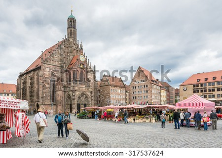 NUERNBERG, GERMANY - SEPTEMBER 5: Tourist at the Frauenkirche in Nuernberg, Germany on September 5, 2015. The church is a brick gothic architecture built in the 14th century.  - stock photo