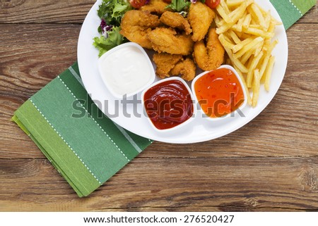 Nuggets and chips on a plate served with dip and salads on a wooden board