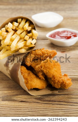 Nuggets and chips served in a paper bag with a dip on a wooden board