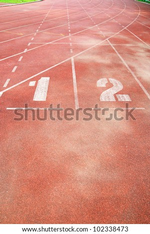 number 1 and 2 on running track ,number on start point of running track background, Red running track in stadium. Running track on blue sky.  athletic sport competition