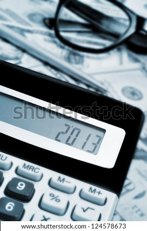 number 2013, as the new year, on the display of a calculator, with some dollar bills in the background